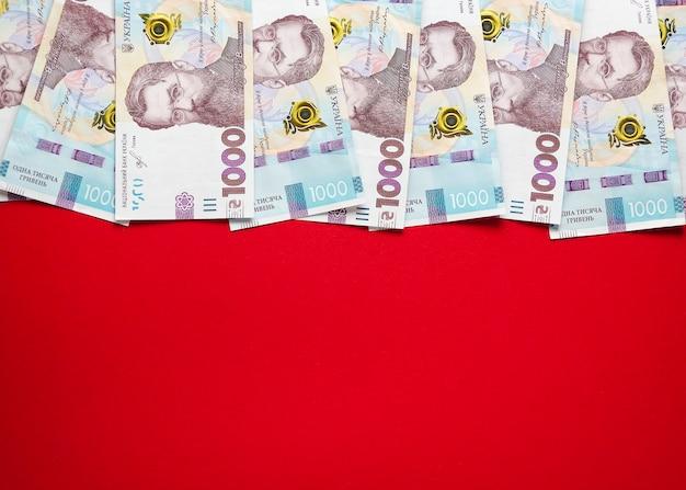 Tysiąc banknotów hrywny ukraińskiej na czerwonym tle