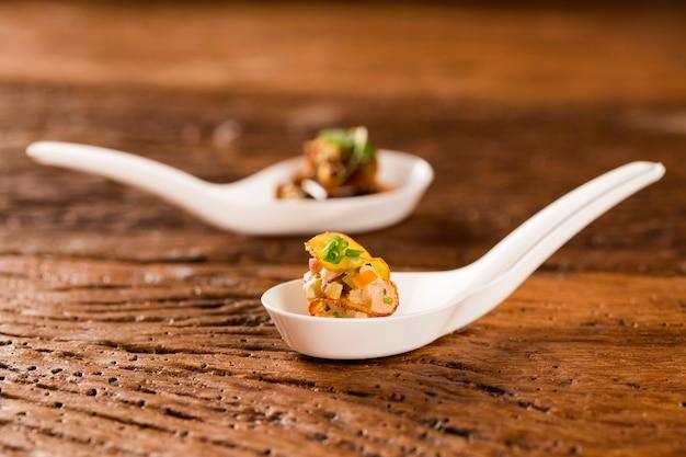 Tysiąc liści bataty, wędzony tuńczyk i ogórki ogórkowe w łyżce. zasmakuj kulinarnych przekąsek