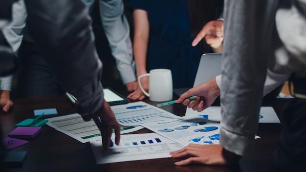 Tysiącleci azjatyccy biznesmeni i biznesmeni spotykający burzę mózgów pomysłów na temat nowych współpracowników projektu papierkowej roboty współpracujących przy planowaniu strategii sukcesu cieszą się pracą zespołową w małym nowoczesnym nocnym biurze.