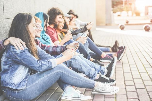 Tysiącleci przyjaciele używają smartfonów siedzieć na zewnątrz