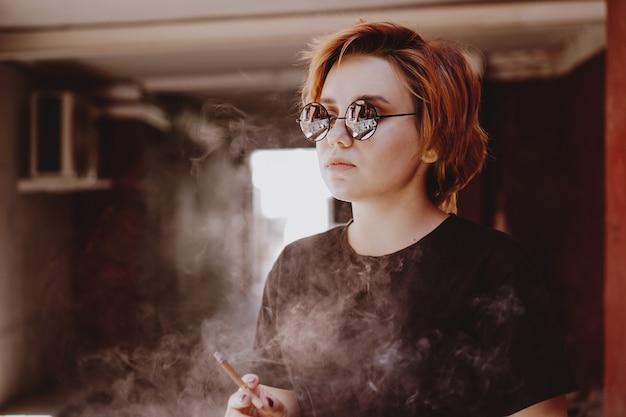 Tysiąclecia fajna ładna dziewczyna z krótkimi rudymi włosami i lustrzanymi okularami, paląca papierosa na starym mieście z czerwonymi ścianami