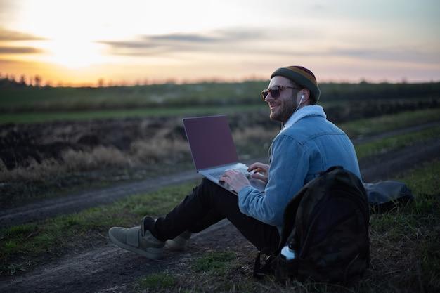 Tysiąclecia hipster człowiek pracuje na laptopie ze słuchawkami w polu o zachodzie słońca