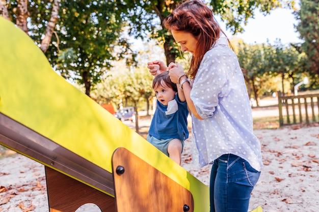 Tysiąclecia mama pomaga swojemu rocznemu synowi wspinać się na zjeżdżalnię, aby zachować równowagę.