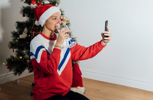 Tysiąclecia młoda kobieta używa telefonu w domu w wigilię bożego narodzenia. internetowe zakupy świąteczne, kwarantanna