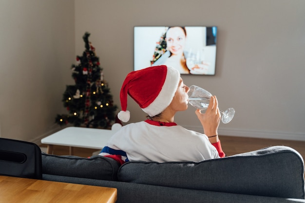 Tysiąclecia Młoda Kobieta Używa Telefonu W Domu W Wigilię Bożego Narodzenia. Internetowe Zakupy świąteczne, Kwarantanna Premium Zdjęcia