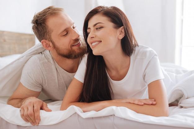 Tysiącletni mężczyzna i kobieta uśmiechają się szeroko, leżąc w łóżku i rozmawiając o swoich związkach