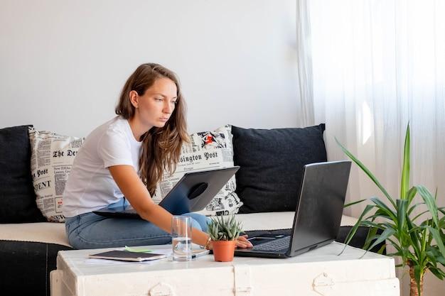 Tysiącletnia kobieta pracuje w domu, siedzi blisko laptopa z notebookiem, szklanką wody na białym stole w domowym obszarze roboczym.
