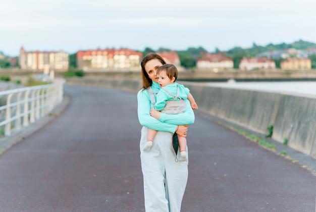 Tysiącletnia młoda dorosła kobieta trzyma swoje dziesięciomiesięczne dziecko, ciesząc się popołudniem o zachodzie słońca