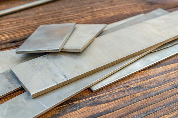 Tytanowe stopy talerze bary szpilki zapasu dziury tubki rzemienia arkusz dla noża rękojeści noża robi materiały zaopatrzeniowe na brown drewnianym tle