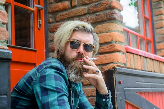 Tytoń stylowy brodaty mężczyzna z papierosem palący hipster zmysłowy brodaty mężczyzna z papierosem