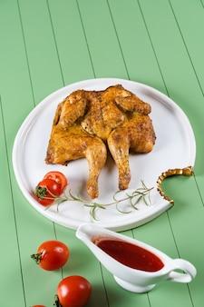 Tytoń z kurczaka z sosem pomidorowym, rozmarynem i pomidorami na pięknym białym talerzu na zielonym stole. grillowany kurczak.