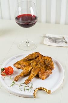 Tytoniowy kurczak na białym talerzu z lampką czerwonego wina, sztućce. grillowany kurczak.