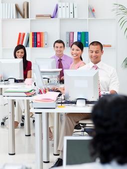 Uśmiechnięci ludzie biznesu pracuje przy komputerami