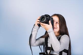 Uśmiechnięta dziewczyna fotografuje przez kamery przeciw błękitnej kamerze