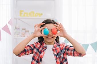 Uśmiechnięta dziewczyna trzyma czerwonych i błękitnych Easter jajka nad jej oczami w domu