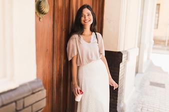 Uśmiechnięta dziewczyna trzyma rozporządzalną filiżankę