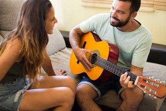 Uśmiechnięta kobieta patrzeje jej męża bawić się gitarę