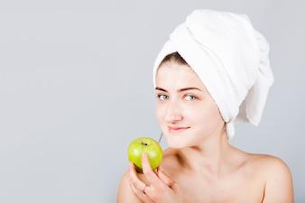Uśmiechnięta kobieta w ręcznikowym mienia jabłku