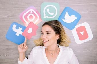 Uśmiechnięta kobieta wskazuje w górę przed ścianą z ogólnospołecznymi networking ikonami