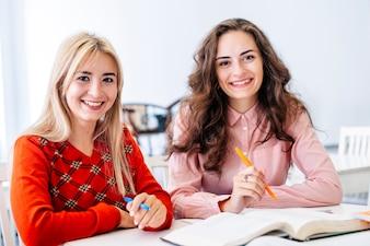 Uśmiechnięte kobiety studiuje w bibliotece