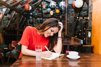 Uśmiechnięty kobiety writing rozkład w dzienniczku z filiżanką kawy na biurku
