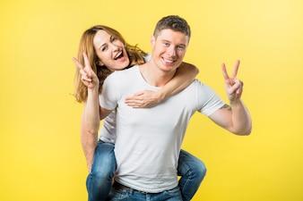Uśmiechnięty mężczyzna niesie jej dziewczyny piggyback przejażdżkę robi zwycięstwo znakowi