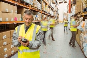 Uśmiechnięty męski kierownik używa handheld w wielkim magazynie