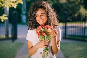 Uśmiechnięty młodej kobiety mienia kwiatu bukiet w ręce