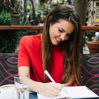 Uśmiechnięty młodej kobiety writing rozkład w dzienniczku