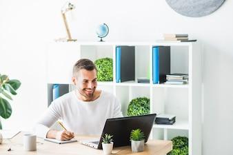 Uśmiechnięty młody biznesmen używa laptop podczas gdy pisać na notepad