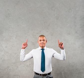 Uśmiechnięty młody biznesmen z jego rękami podnosić wskazujący jego palec up przeciw szarej ścianie