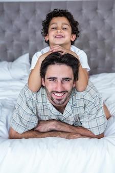 Uśmiechnięty ojciec i syn na łóżku