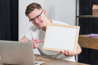 Uśmiechnięty portret młodego człowieka wideo gawędzenie pokazuje drewnianą obrazek ramę