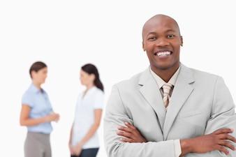 Uśmiechnięty sprzedawca z założonymi rękami i współpracownikami za nim