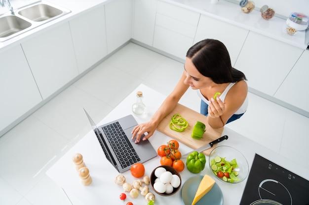 U góry nad zdjęciem pod wysokim kątem pozytywnej, wesołej gospodyni domowej, która chce przygotować kolację, użyj laptopa wyszukaj przepis wegetariański organiczny obejrzyj filmy o kuchni w białej kuchni w domu