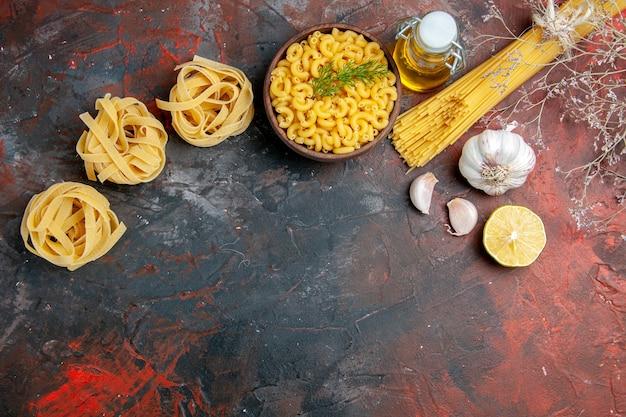 U góry widok niegotowanych trzech porcji makaronu spaghetti i motylkowego w brązowej misce i butelce z olejem czosnkowym i zieloną cebulą na stole o różnych kolorach