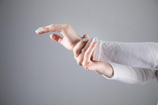 U młodej kobiety bolą nadgarstki na szarej scenie