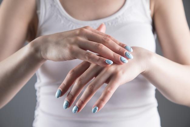 U młodej kobiety palce bolą na szarej ścianie