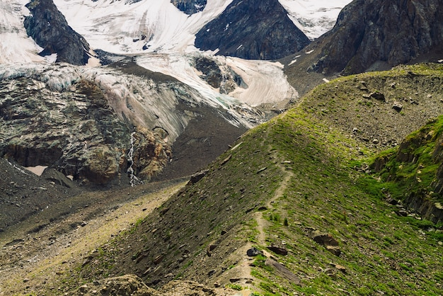U podnóża gigantycznego lodowca. niesamowita ogromna skalista naturalna ściana. skalista płaskorzeźba ze śniegiem i lodem w kształcie dużego płaczącego oka. ścieżka w górach. cudowne fantastyczne dzieła sztuki o majestatycznej naturze