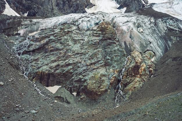 U podnóża gigantycznego lodowca. niesamowita skalista płaskorzeźba ze śniegiem i lodem. cudowna ogromna skalista naturalna ściana z małymi wodospadami. woda z lodowca. fantastyczna grafika majestatycznej góralskiej przyrody.