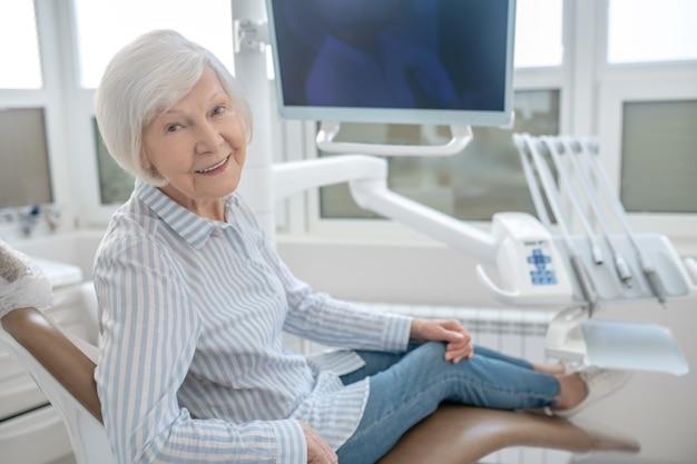 U trzech lekarzy. siwowłosa kobieta siedzi w gabinecie dentystycznym i czeka na lekarza