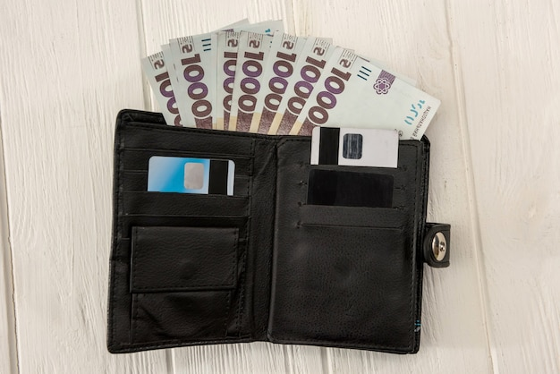 Uah, czarny męski portfel jest pełen pieniędzy. uah pieniądze ukrainy 1000 i 500 banknotów na biurku. koncepcja pieniędzy i oszczędności