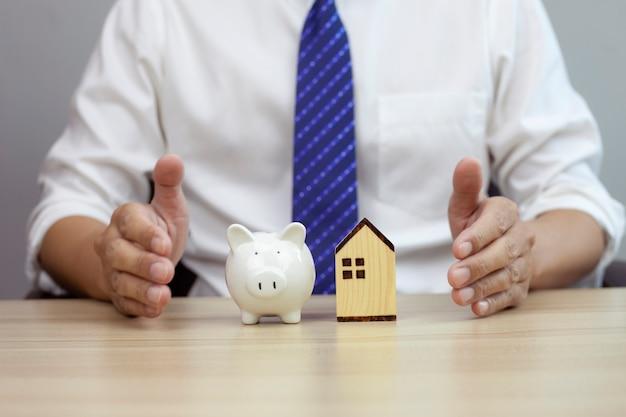 Ubezpieczenie koncepcji bezpieczeństwa domu i świnki dla nieruchomości chroniących gest człowieka i domu