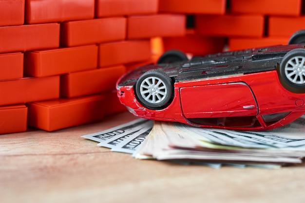 Ubezpieczenie na życie w koncepcji wypadku samochodowego. zepsuty samochód i banknoty dolarowe