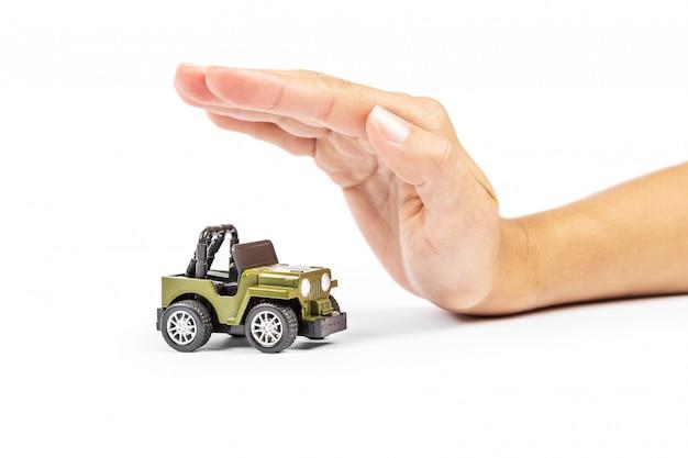 Ubezpieczenie samochodu. miniatura samochodu zakryta rękami.
