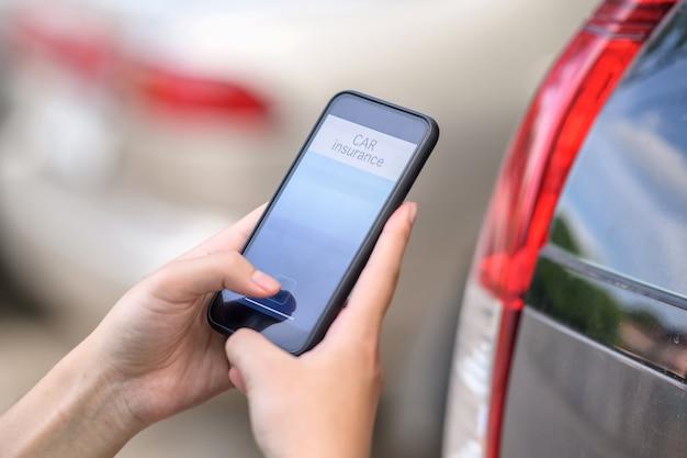 Ubezpieczenie samochodu pojęcie, mężczyzna ręki mienia ubezpieczenia samochodu zastosowanie na telefonie komórkowym.