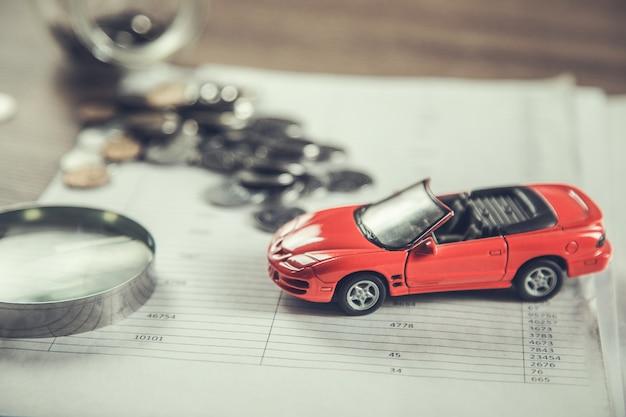 Ubezpieczenie samochodu z monetami na dokumencie
