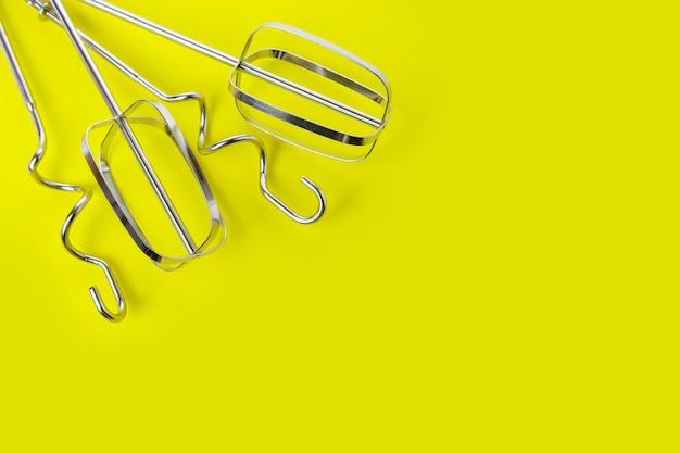 Ubijaki i haki do ciasta do miksera stojącego na żółtym tle, widok z góry, miejsce na kopię. koncepcja pieczenia.