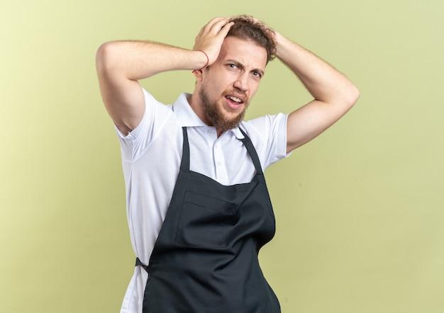 Ubolewany młody męski fryzjer ubrany w mundur chwycił głowę odizolowaną na oliwkowozielonym tle