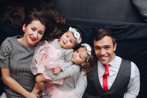 Ubrana młoda para uśmiechnięta, leżąca na łóżku z uroczymi dziećmi między nimi